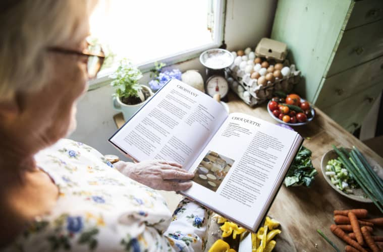 Happy elderly woman reading a cookbook